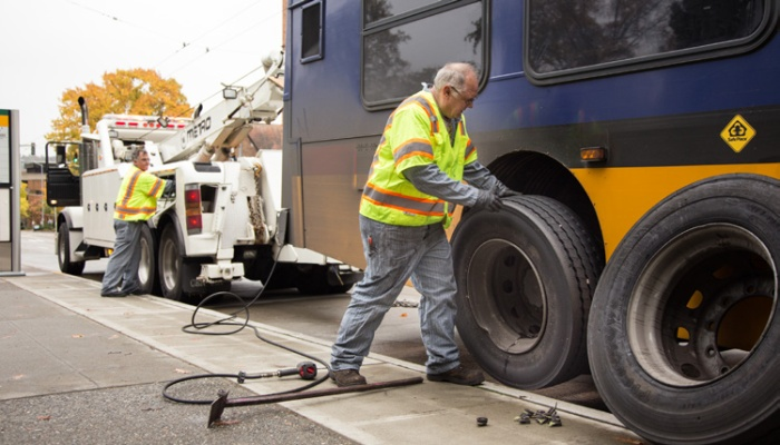 Atlantic Base mechanic Dave Bankson, left, uses the wrecker to lift a disabled bus while Central Base mechanic Walter Olson removes a damaged tire.