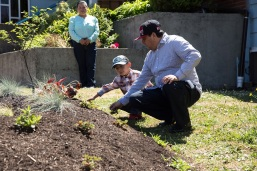 A Hispanic family pictured with the RainWise garden achieved through their church.