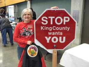 Linda Romanovitch, the first woman carpenter at King County, holds a jobs sign and union jacket at a past Fair.