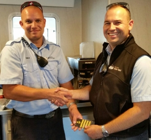 Pictured: Nick Williams, on the left, receiving Captains epaulets from Deckhand/Relief Captain GW Rogers.