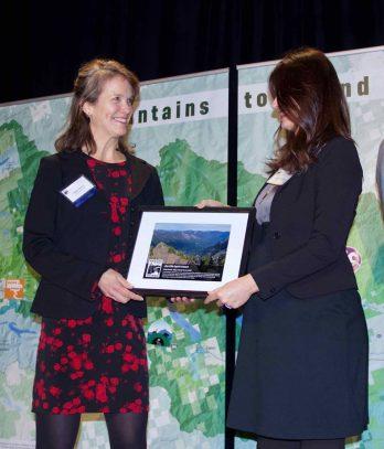 Pictured: Kelly receiving the Jim Ellis Spirt Award from Jim's granddaughter Hayley Goelzer.